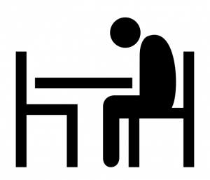 Picture of person sitting alone at a table with head bowed